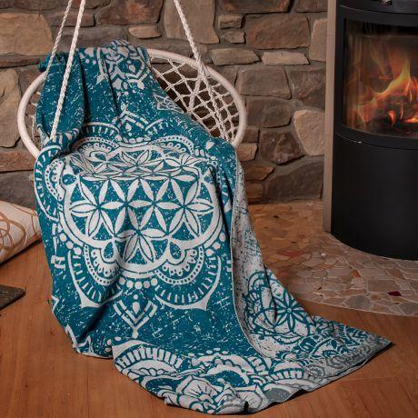 Kuscheldecke aus Bio-Baumwolle in Hängestuhl, vor Kaminfeuer und Steinwand. Motiv Blume des Lebens auf Decke