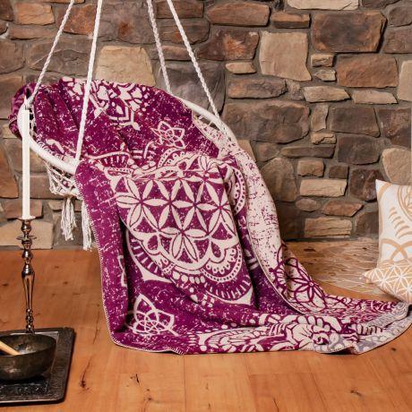 Kuscheldecke aus Bio-Baumwolle in der Farbe beere in Hängestuhl vor Steinwand. Motiv der Blume des Lebens auf Decke.