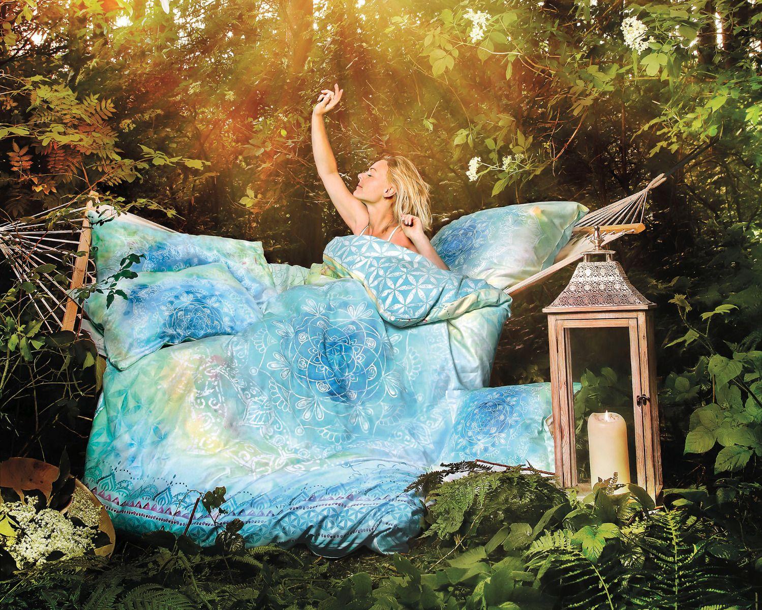 Bio-Bettwäsche in blau grün auf Hängematte im Wald. Blonde Frau streckt sich genüsslich. Kissen, Dekoration, Blüten, Kerzen
